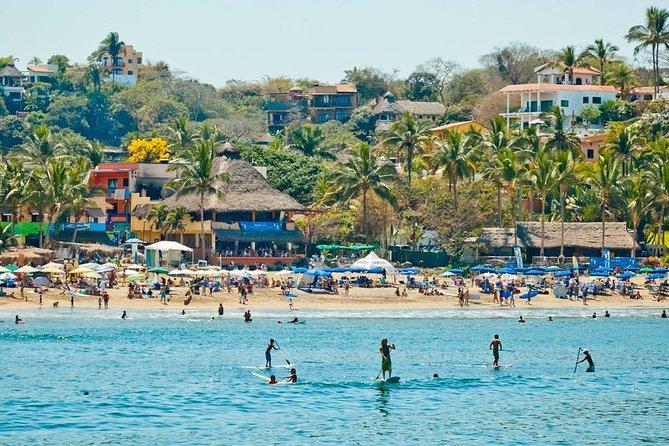 La Lancha beach in Sayulita, you can see surfers and tourists around.
